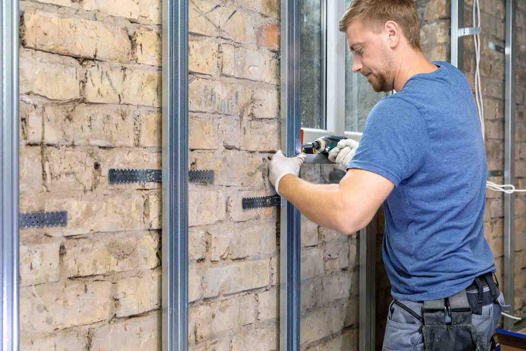 Mann monterer installasjon til veggen
