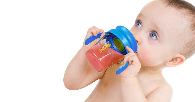 Small child drinks red juice of blue drinking cup